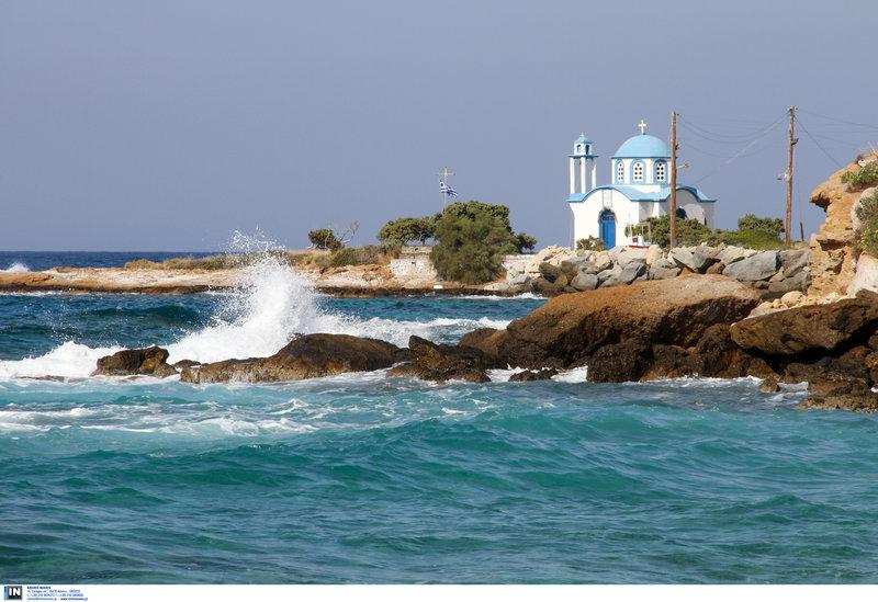 Κύματα σκάνε στα βράχια της Ικαρίας με φόντο ένα εκκλησάκι πλάι στη θάλασσα
