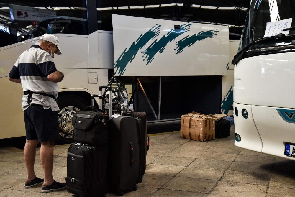 Επιβάτες με αποσκευές έξω από λεωφορεία του ΚΤΕΛ