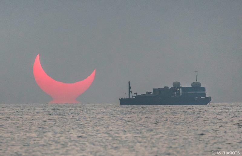 Ο φωτογράφος θέλησε να τραβήξει την στιγμή που ο ήλιος θα αναδυόταν από την θάλασσα ,γι' αυτό και επέλεξε ένα σημείο με ανοιχτό ορίζοντα