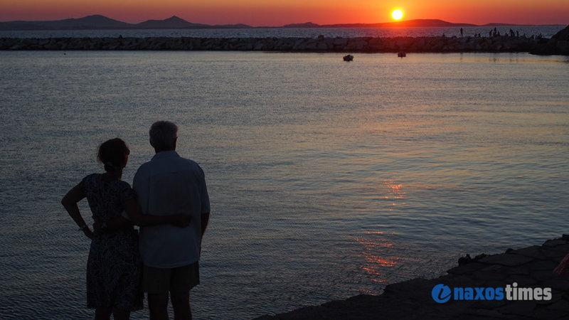 Ζευγάρι παρακολουθεί το ηλιοβασίλεμα στη Νάξο