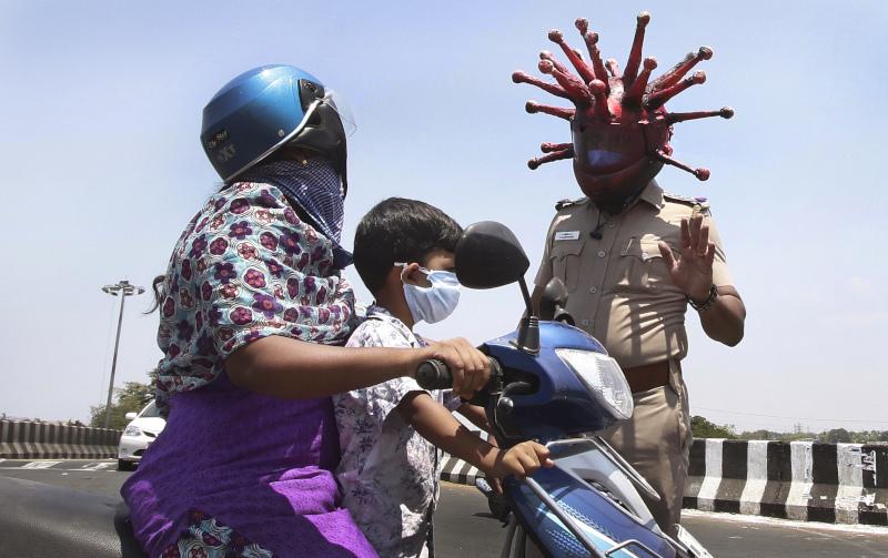 Ο Ινδός αστυνομικός Ρατζές Μπαμπού φοράει κράνος που αντιπροσωπεύει τον κορωνοϊό και ζητά από τον κόσμο να παραμείνει στο σπίτι
