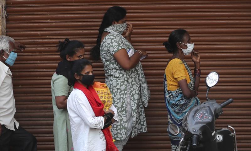 Γυναίκες και άνδρες με μάσκες στην Ινδία