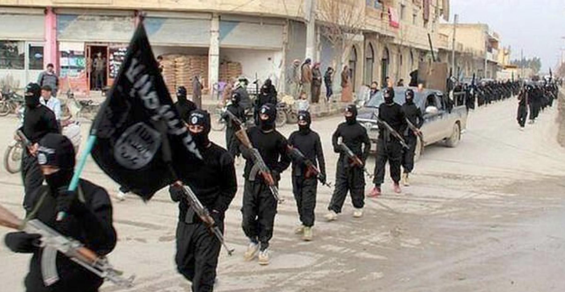 Μαχητές του ISIS παρελαύνουν με όπλα και σημαίες στη Ράκα της Συρίας το 2014.