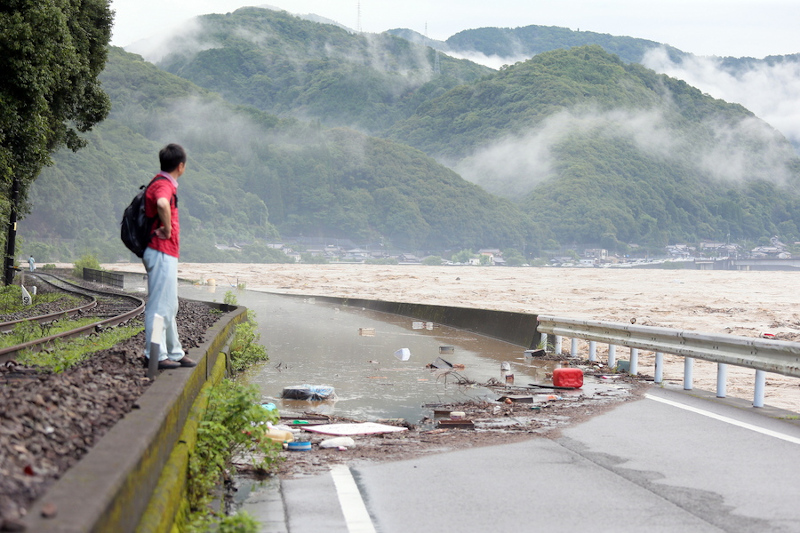 Άνδρας παρατηρεί ποτάμι που υπερχείλισε