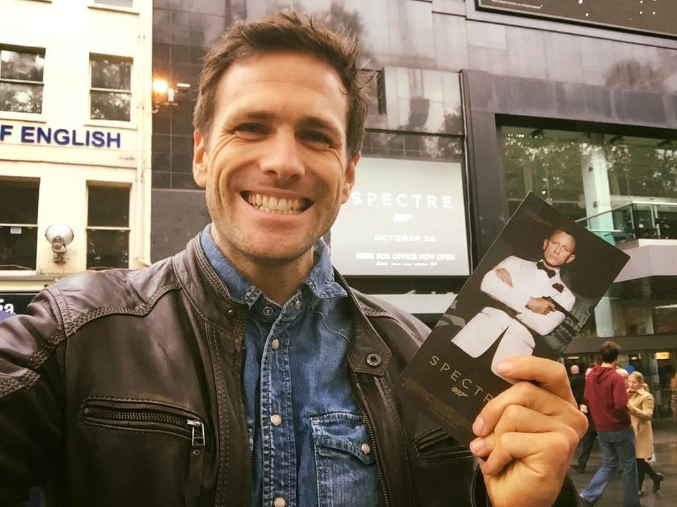 Ανδρας χαμογελά κρατώντας ένα εισιτήριο της ταινίας Spectre