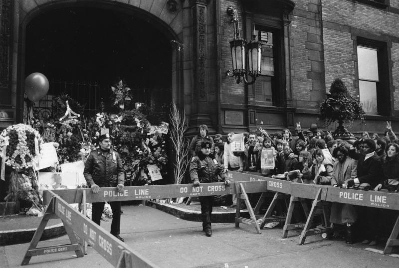 Η είσοδος της πολυκατοικίας όπου διέμενε ο Τζον Λένον. Λίγες ώρες μετά την ανακοίνωση του θανάτου του, η αστυνομία προσπαθεί να συγκρατήσει τους οπαδούς των Beatles