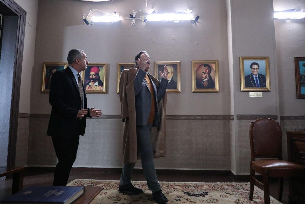 Ο Περίανδρος Πώποτας εισβάλει στο Δημαρχείο, στους τοίχους του οποίου υπάρχει ένα κάδρο με το πορτρέτο του