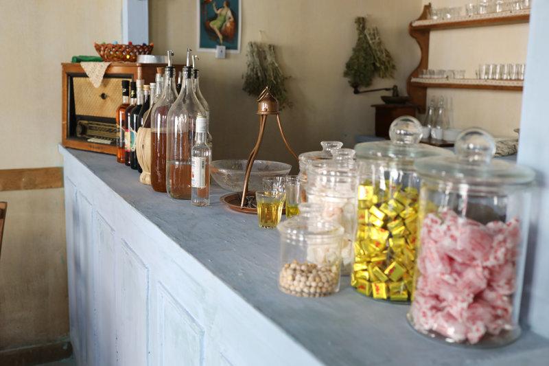 Ο πάγκος του καφενείου με τις μποτίλιες, το ραδιόφωνο, τον παραδοσιακό δίσκο και τις γυάλες με τις καραμέλες στις «Άγριες Μέλισσες»