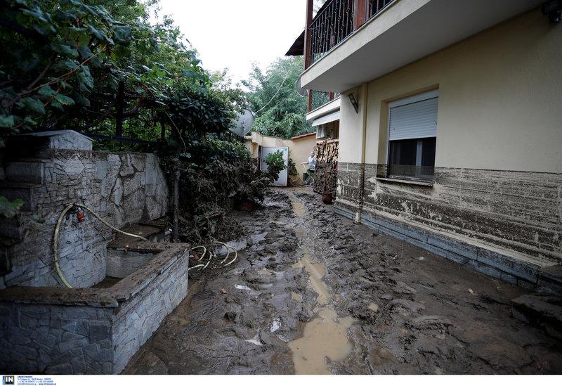 Με ένα λάστιχο κάτοικος στην Ευκαρπία Θεσσαλονίκης προσπαθεί να καθαρίσει τις λάσπες από την αυλή του σπιτιού του