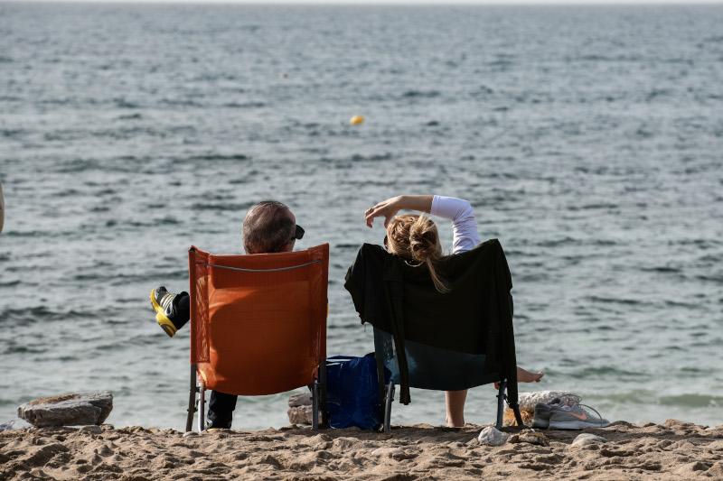 ζευγάρι κάθεται σε καρέκλες στην παραλία