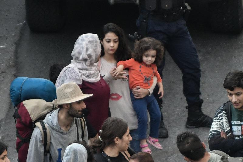 Μία μητέρα κρατάει αγκαλιά την κόρη της και περιμένει να επιβιβαστεί στο πούλμαν