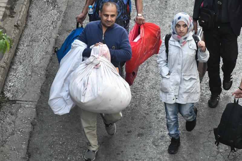Με τα υπάρχοντά τους στα χέρια οι αλλοδαποί εγκαταλείπουν το υπό κατάληψη κτίριο στα Εξάρχεια