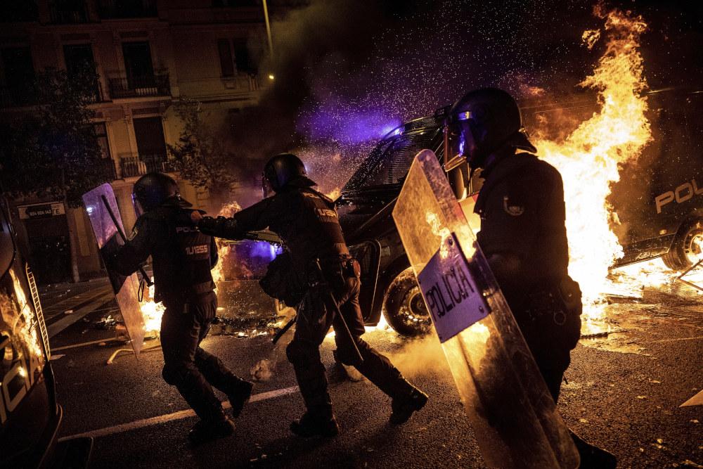 Αστυνομικοί στην Ισπανία με ασπίδες μπροστά σε φωτιές σε επεισόδια στην Καταλονία