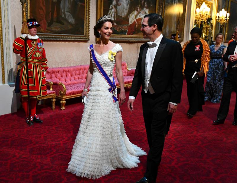 Η Κέιτ Μίντλετον με λευκή τουαλέτα περπατά στο παλάτι του Μπάκιγχαμ