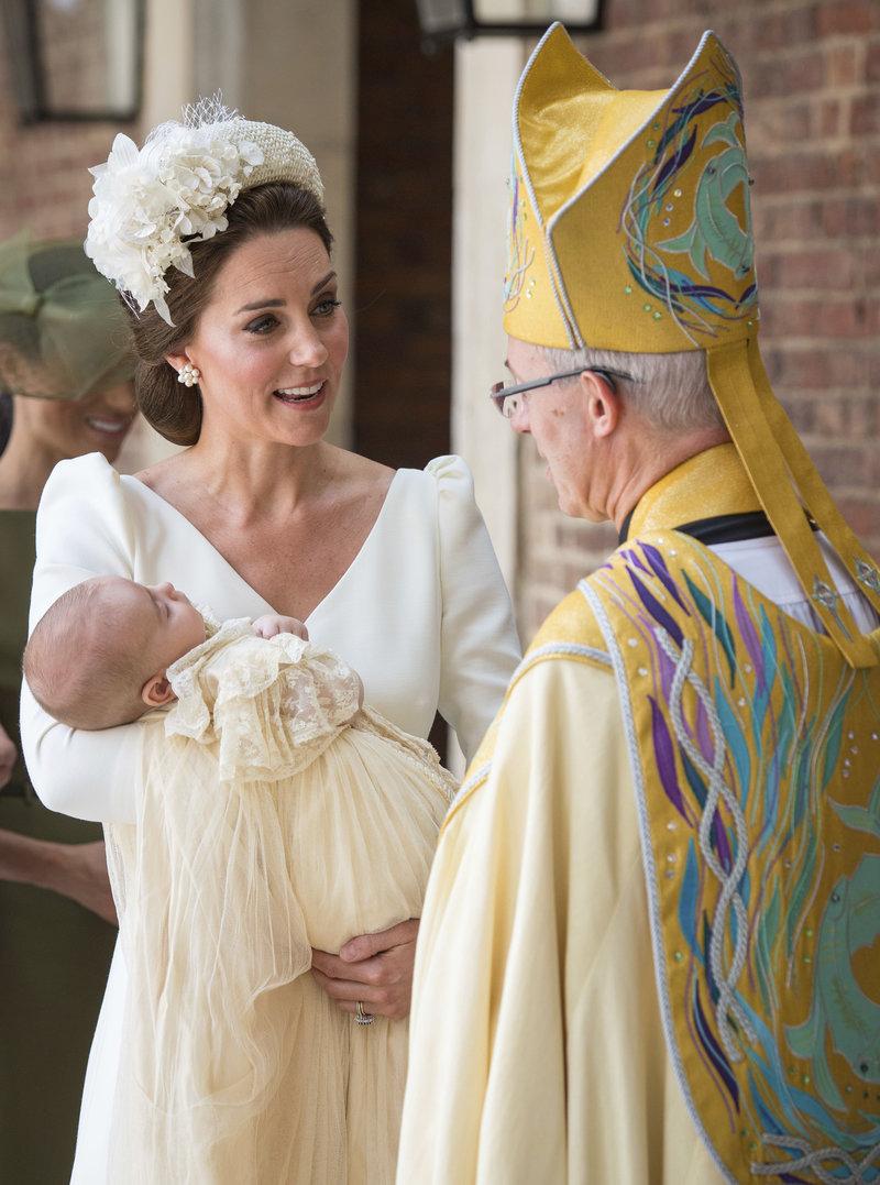 Η Κέιτ Μίντλετον κρατά τον πρίγκιπα Λουίς, ο οποίος φορά το χαρακτηριστικό ρούχο που φορούν όλα τα βασιλικά μωρά στη βάφτισή τους. Δίπλα της, ο Αρχιεπίσκοπος του Κάντερμπέρι, Τζάστιν Γουέλμπι
