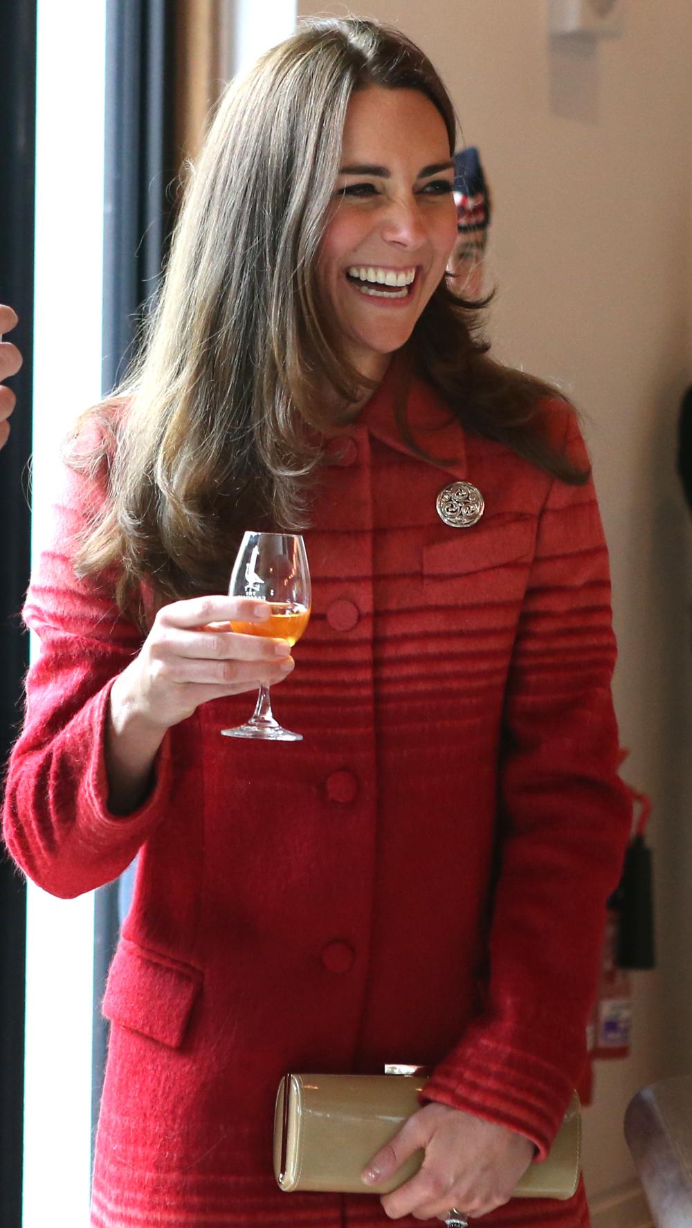 Η Κέιτ Μίντλετον με κόκκινο παλτό πίνει ένα ποτήρι κρασί