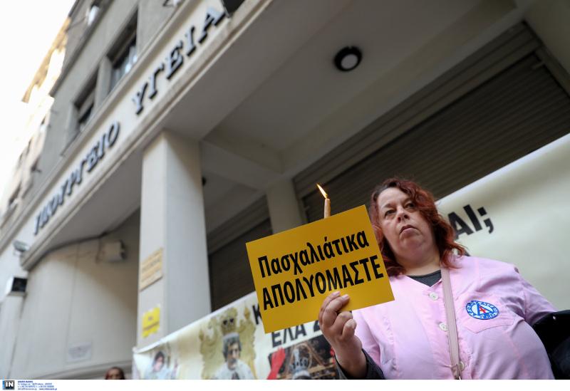 Μια καθαρίστρια με ένα κερί στο χέρι και χαρτί που γράφει «Πασχαλιάτικα απολυόμαστε»