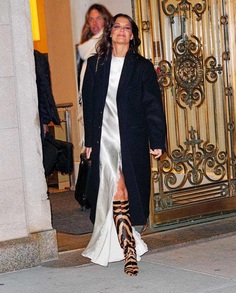 Κέιτι Χολμς με λευκό σατέν φόρεμα και μαύρο παλτό
