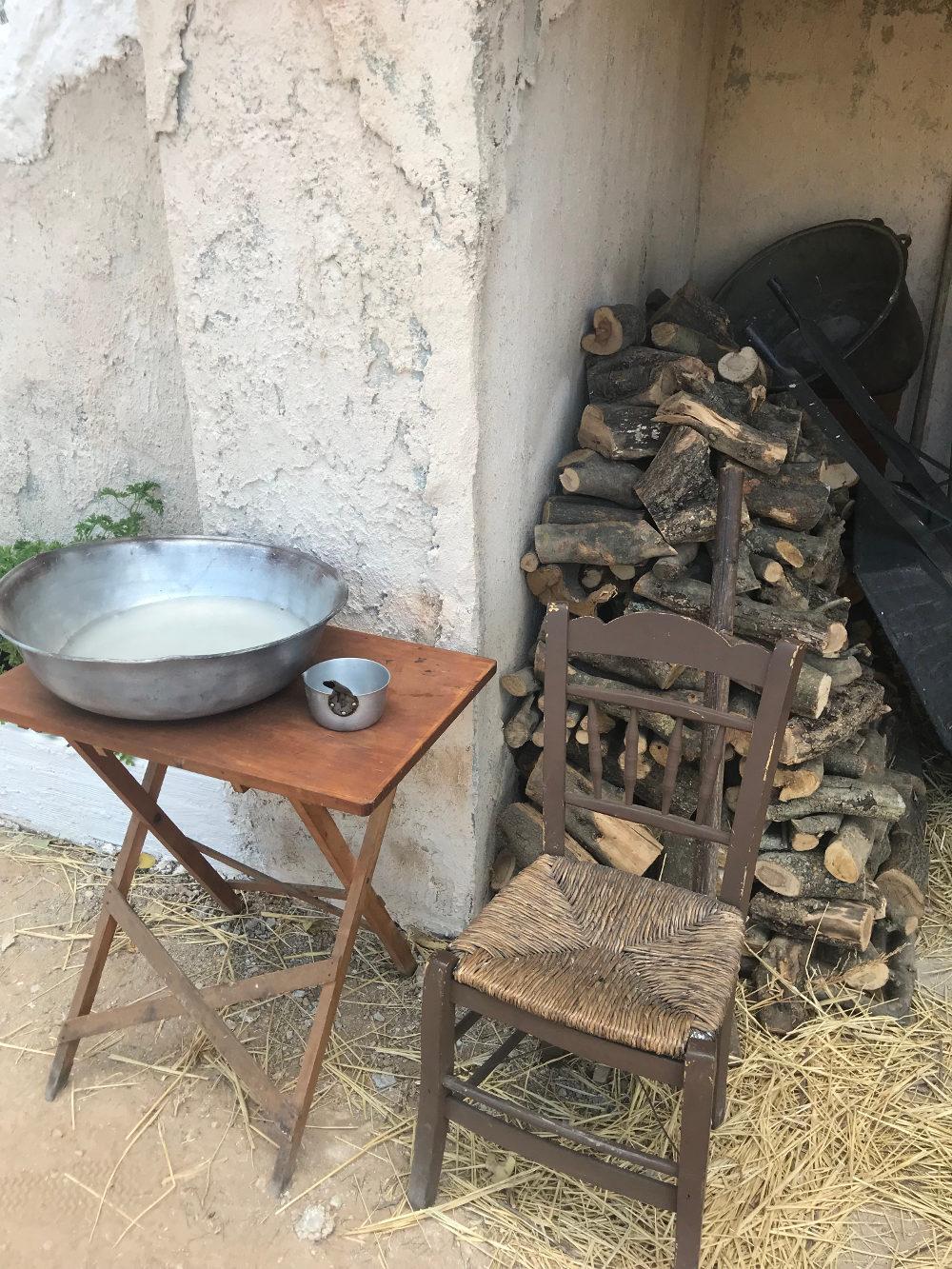 Μια παλιά καρέκλα με ψάθινη θέση και γαλβανισμένα σκεύη στο σκηνικό της σειράς «Άγριες Μέλισσες»