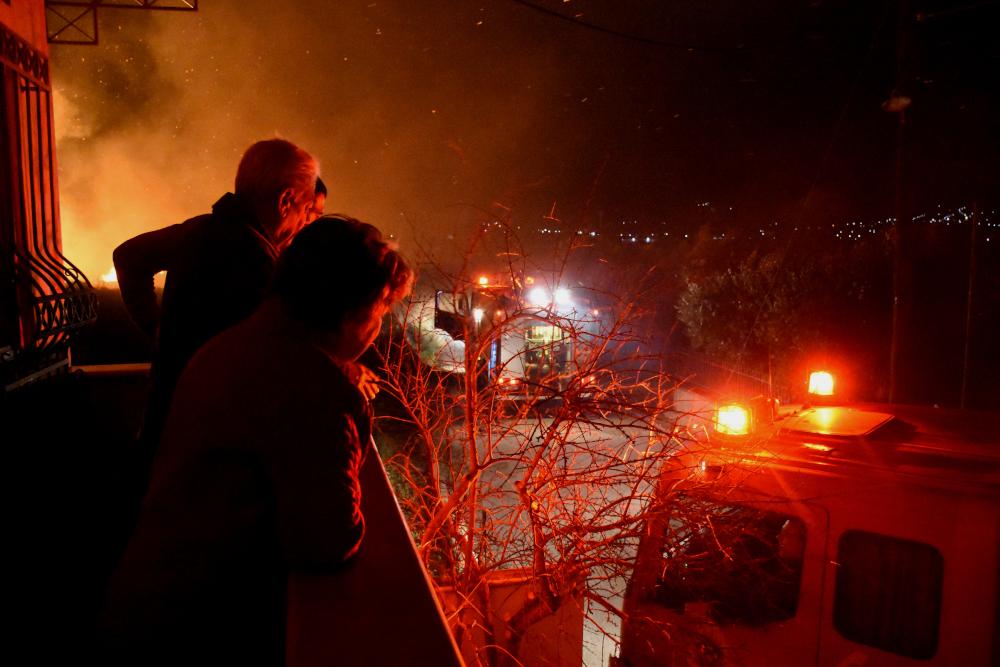 Κάτοικοι κοιτάζουν πυροσβέστες που σβήνουν φωτιά