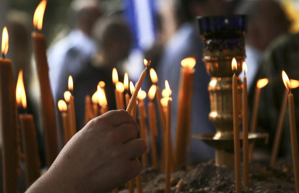 Πιστός ανάβει κερί σε ορθόδοξο ναό