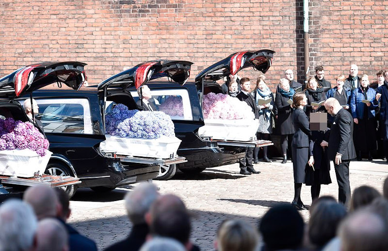 Ο Πόβλσεν παρηγορεί την σύζυγό του Αν και την κόρη του Αστριντ μπροστά από τα φέρετρα των παιδιών τους