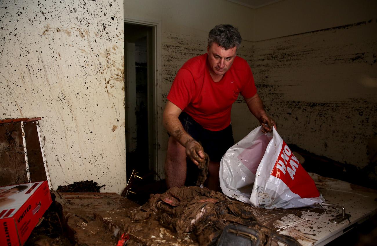 Ανδρας μαζεύει αντικείμενα από λάσπες στο σπίτι του