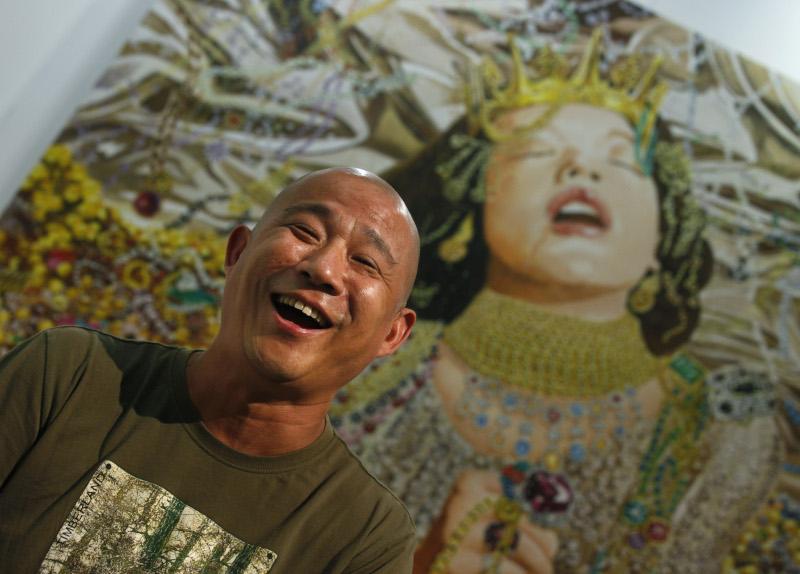 Ο Κινέζος καλλιτέχνης Fang Lijun μπροστά από έναν πίνακά του