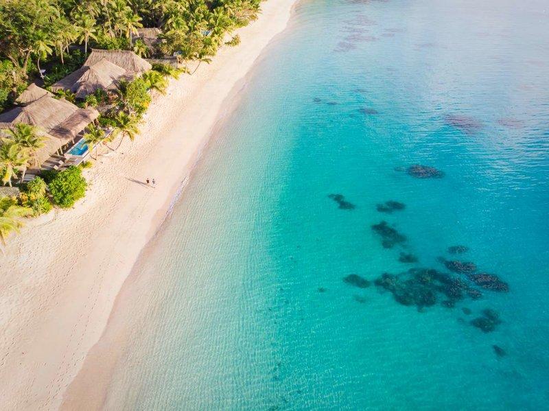 Γαλαζοπράσινα νερά και παραλία με λευκή άμμο