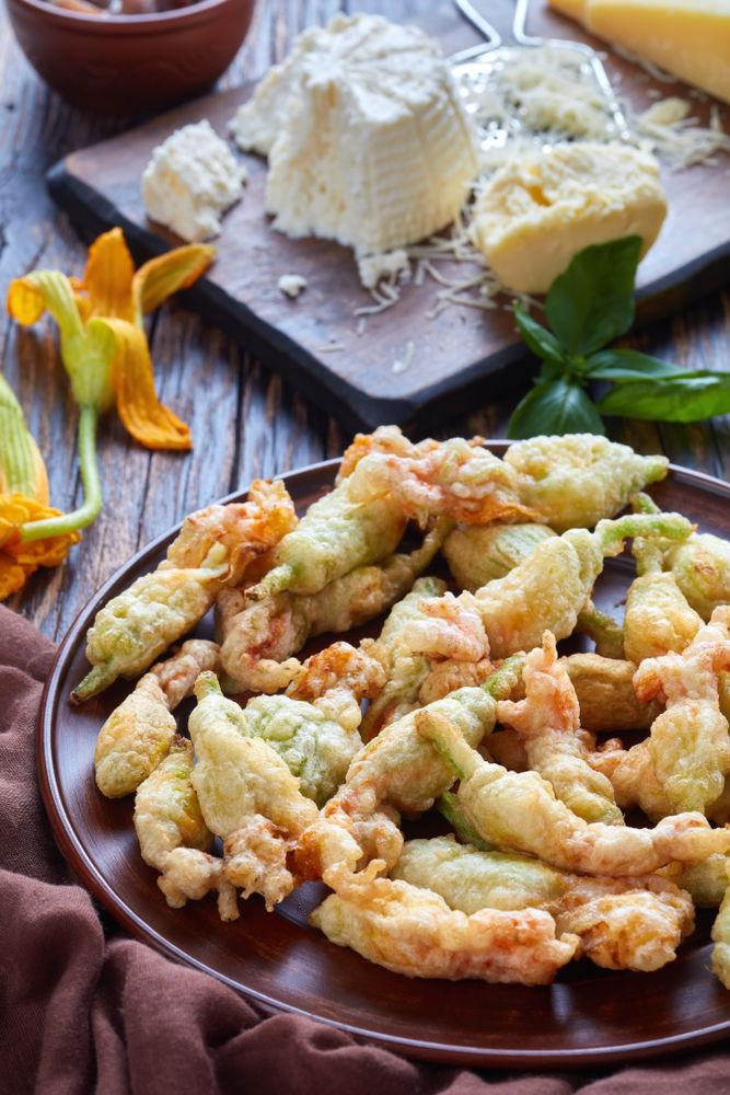 Λουλούδια κολοκυθιού τηγανητά σε πιατέλα πλάι σε τυρί ρικότα και παρμεζάνα