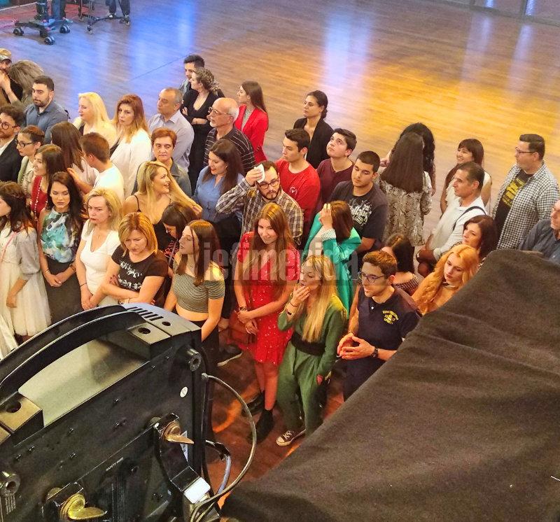 Η κοπέλα του Μανώλη με κόκκινο φόρεμα περιμένει μαζί με το κοινό