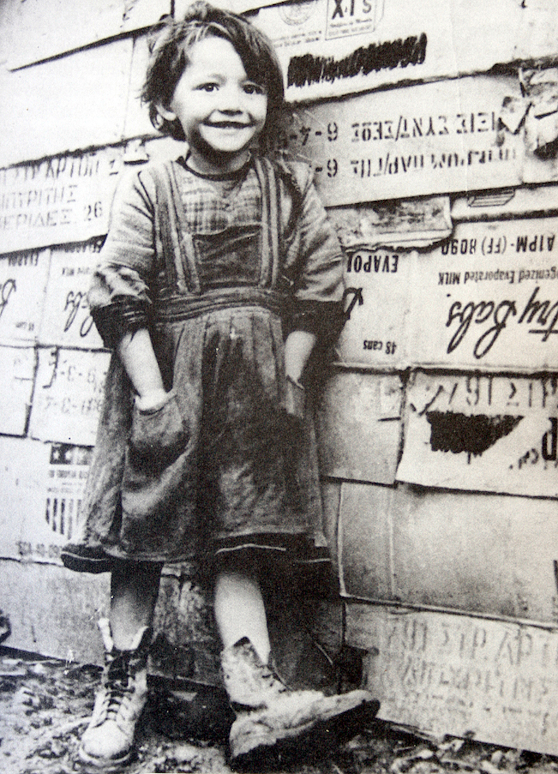 Κοριτσάκι στην Αθήνα του 1943. Πίσω κουτιά με ρούχα και τρόφιμα από την αποστολή του Oxford Committee for Famine Reliefe στην κατεχόμενη Αθήνα (Oxfam fotos).