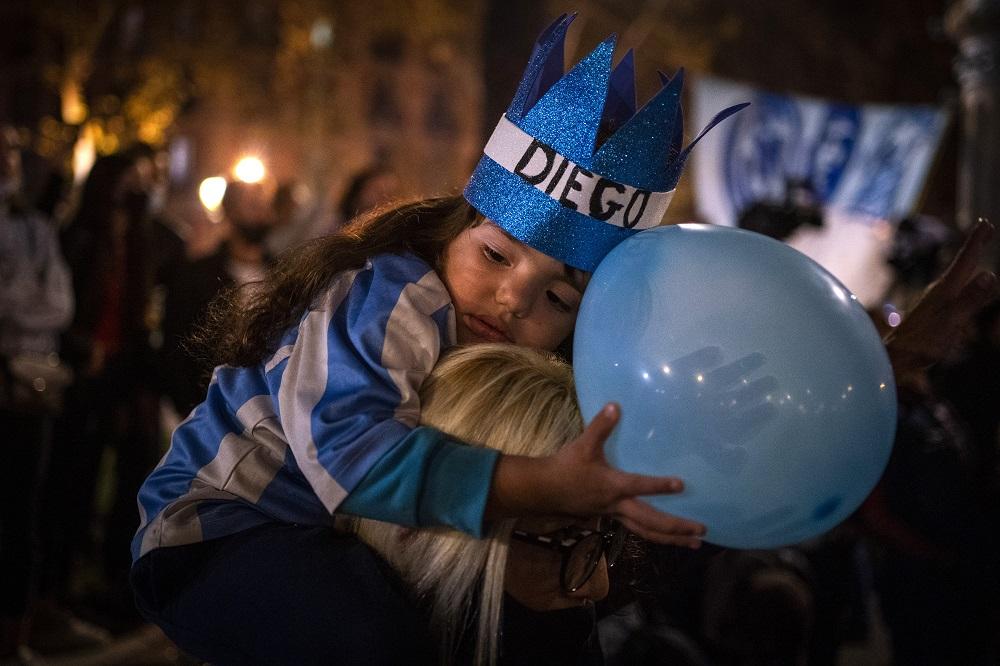 Ένα μικρό κορίτσι στην αγκαλιά της μητέρας της σε ένα μπλουζάκι και καπέλο Maradona