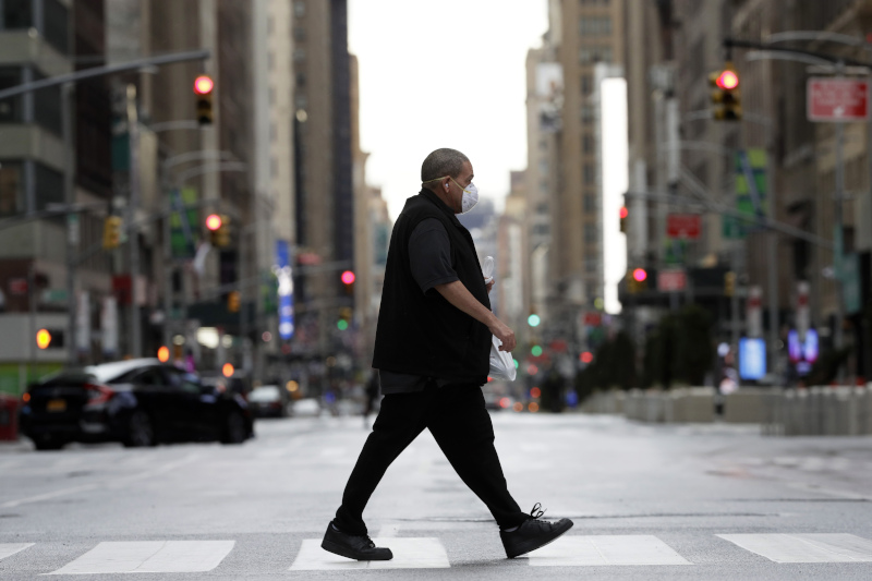 Άνδρας με μάσκα περπατά στους έρημους δρόμους της Νέας Υορκης
