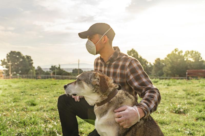 Ανδρας με μάσκα και συνοδεία τον σκύλο του