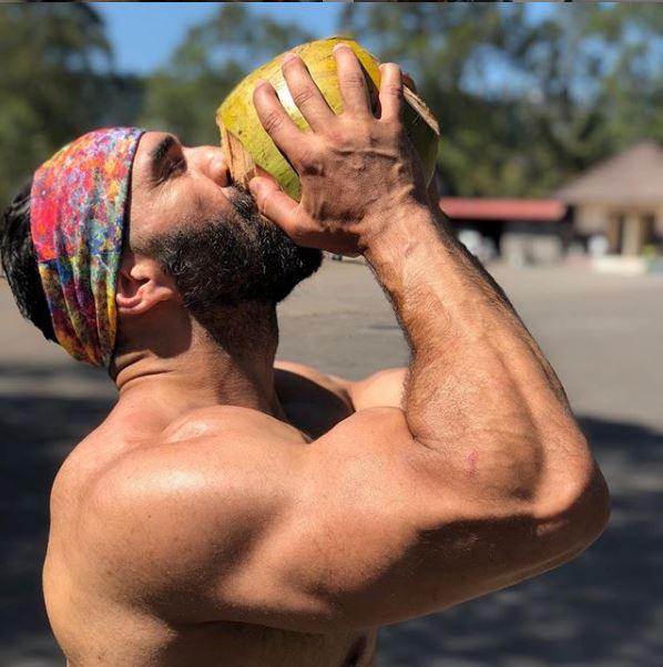 Άνδρας γυμνασμένος πίνει χυμό καρύδας