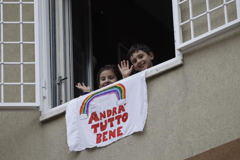 Παιδιά σε μπαλκόνι στην Ιταλία με πανό με ουράνιο τόξο
