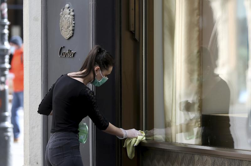 Υπάλληλος καταστήματος στην Αυστρία με μάσκα, ξεσκονίζει την πρόσοψη λίγο πριν το άνοιγμα