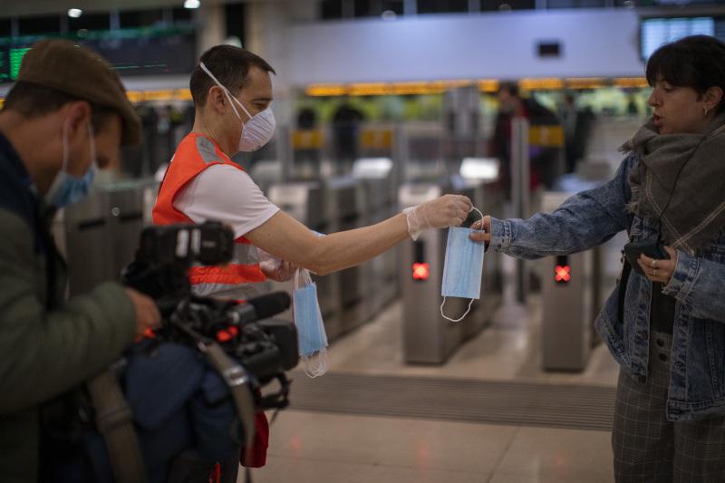 Εθελοντής του Ερυθρού Σταυρού μοιράζει μάσκες στους Ισπανούς που χρησιμοποιούν τα μέσα μεταφοράς
