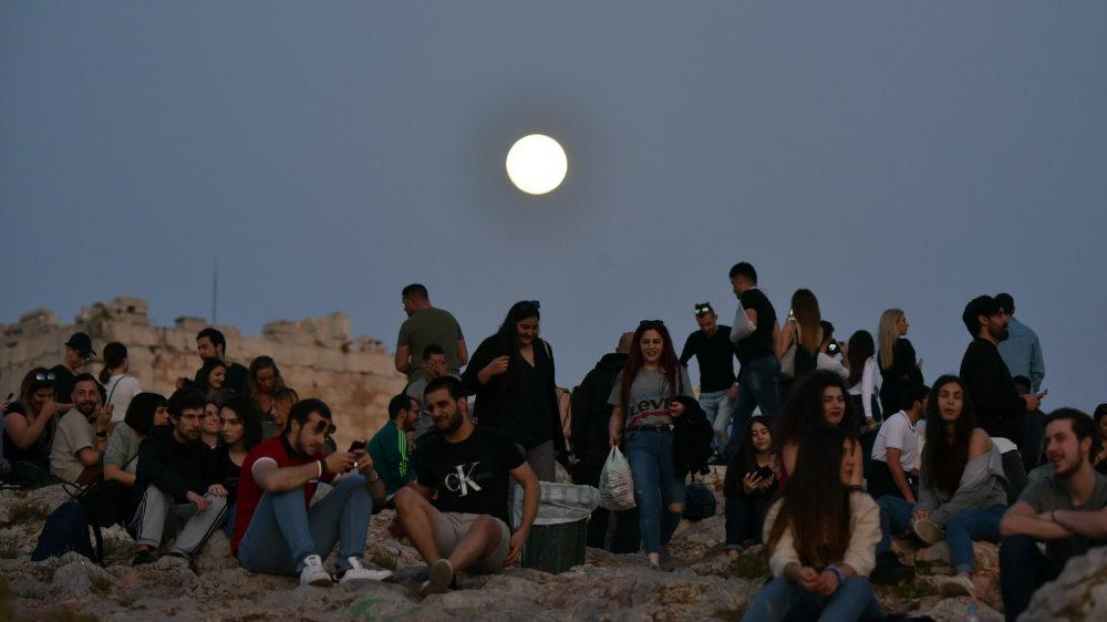Δεκάδες κόσμου στον βράχο της Ακρόπολης το βράδυ της Τετάρτης με φόντο το σχεδόν ολόγιωμο φεγγάρι