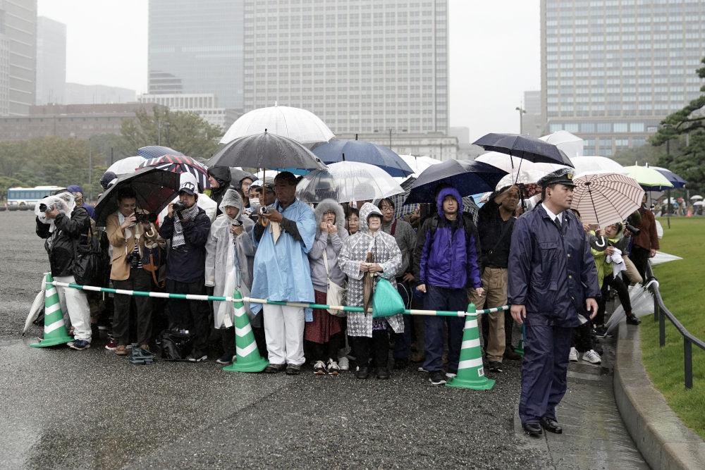 Κόσμος με αδιάβροχα και ομπρέλες περιμένει υπομονετικά να παρακολουθήσει την τελετή ενθρόνισης του αυτοκράτορα της Ιαπωνίας