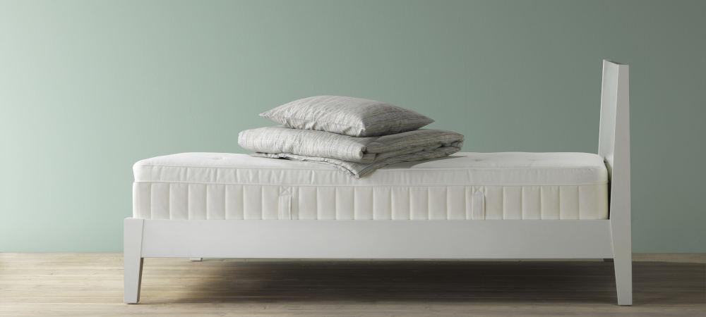 Κρεβάτι στην άκρη ενός βεραμάν τοίχου με πάπλωμα και μαξιλιάρι