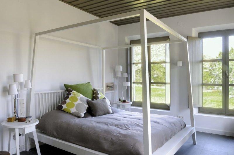 Η κρεβατοκάμαρα με  γκρι πάπλωμα και πράσινα μαξιλάρια