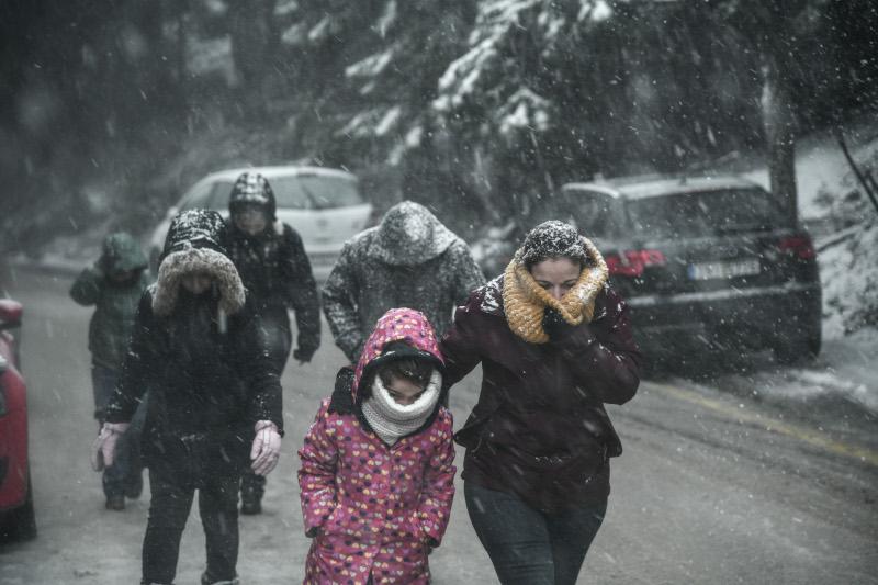 κόσμος ντυμένος με μπουφάν κασκόλ και γάντια στην Πάρνηθα