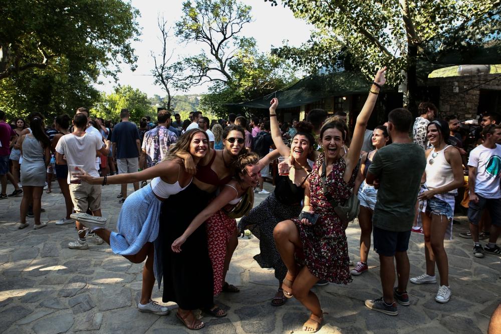 Παρέες με τουρίστες και επισκέπτες στην Λαγκάδα διασκεδάζουν πίνοντας κόκκινο κρασί από τους αμπελώνες του νησιού / Φωτογραφία: Sooc