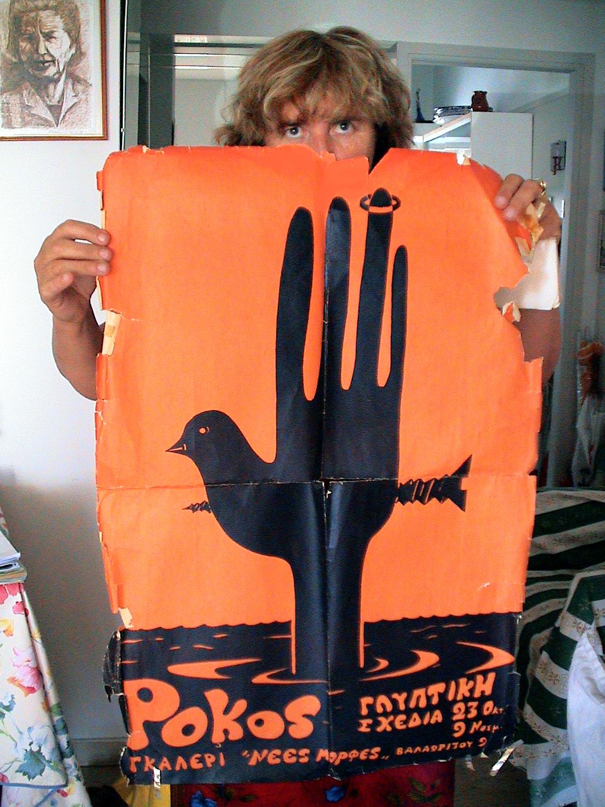 Η Λαοκρατία Λάκκα, στο σπίτι της, κρατά αφίσα με το Περιστέρι της Ειρήνης