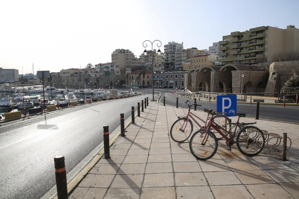 Αδειος δρόμος στο λιμάνι Ηρακλείου με παρκαρισμένα ποδήλατα