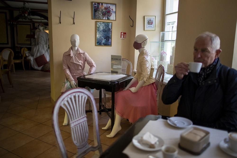Ηλικιωμένος πίνει καφέ δίπλα σε κούκλες βιτρίνας σε εστιατόριο