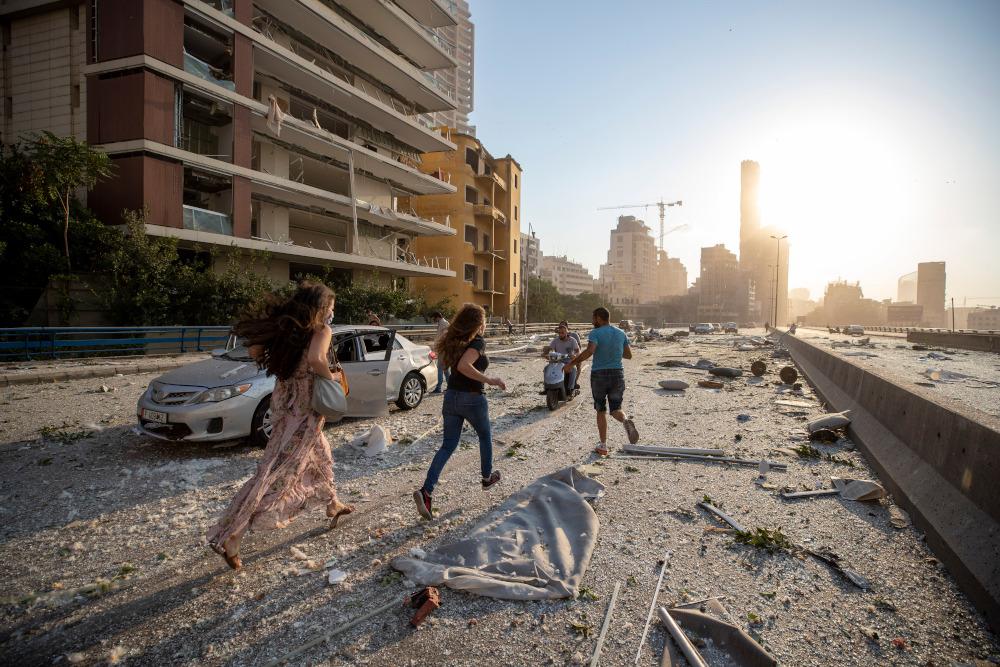 Πολίτες τρέχουν δίπλα σε συντρίμμια σε δρόμο της Βηρυτού