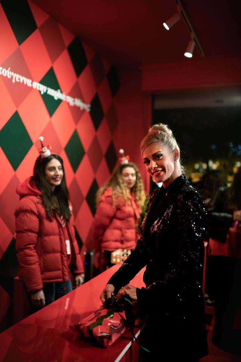 Η Ζέτα Μακρυπούλια τυλίγοντας δώρα που η Coca-Cola θα μοιράσει σε συνανθρώπους μας